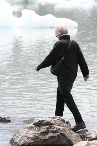 Woman walking on rocks in water by a glacier