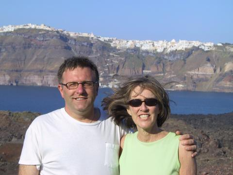 Couple smiling below the cliffs of Santorini