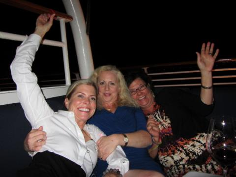 Three women celebrate a lively evening aboard their yacht