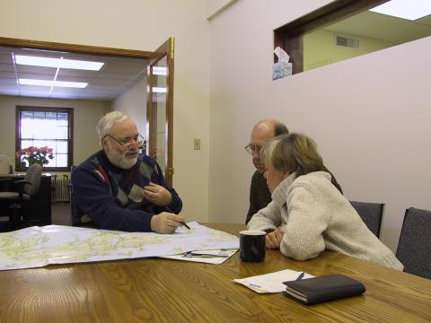 Leftheris reviews a map during a consultation with a couple