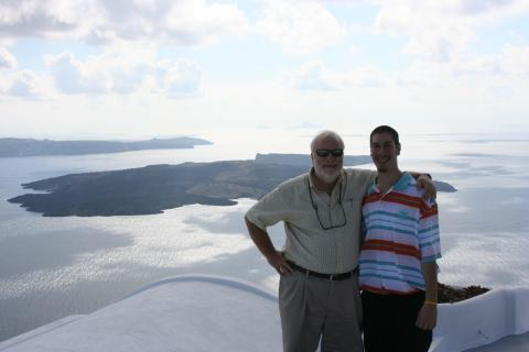 Leftheris and his son Alexandros with shimmering sea and islands below them.