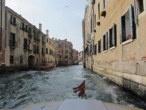 A water taxi moves through a canal in Venice.