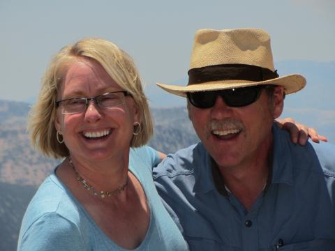 A couple smiles brightly with the cliffs of Santorini behind them.