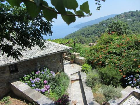 A view over a wall on the greenery and sea of Pelion