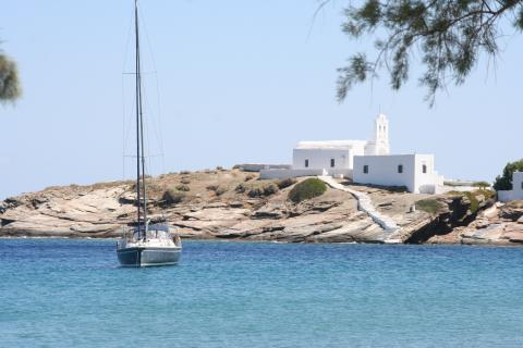 A sailboat sits in the azure waters along the shores, where a white church watches